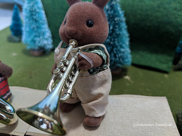 Sylvanian Families Herb Wildwood plays the trumpet. An orthodontic rubber band holds the instrument on his hand